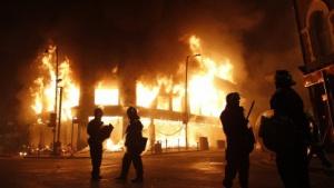 Polizisten vor einem brennenden Gebäude im Londoner Stadtteil Tottenham.