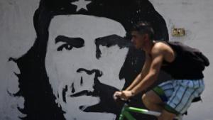 Radfahrer im Juni 2011 in Havanna vor einem Bild von Che Guevara
