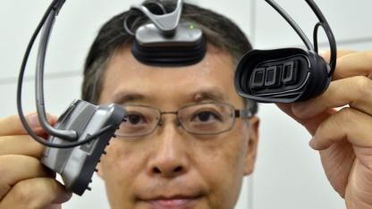 Hitachi-Ingenieur Takeshi Ogino demonstriert den Hirnscanner.