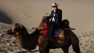 In Zukunft auch WLAN: chinesischer Mobiltelefonierer auf einem Kamel in der Wüste