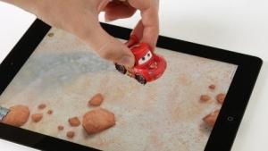 Ein Lightning McQueen aus Plastik saust über das virtuelle Spielfeld.