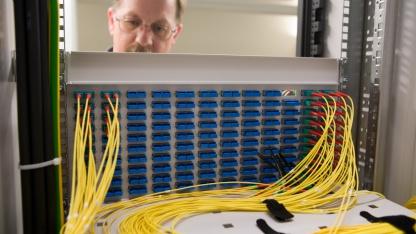 Telekom-Techniker am Glasfaser-Kabelschrank