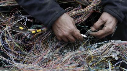 British-Telecom-Beschäftigter repariert Kabel in London.