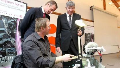 Telekom-Monteur Peter Wagner zeigt Niek Jan van Damme, Telekom, (r.) und Reiner Gebhardt, Chef von Eins, wie Glasfaserkabel zusammengeschweißt werden.