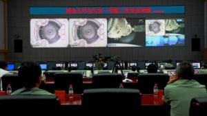 Techiker im Kontrollzentrum Jiuquan verfolgen auf einem großen Bildschirm das Andockmanöver.