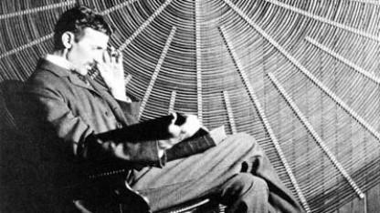 """Nikola Tesla mit Rudjer Boscovichs Buch """"Theoria Philosophiae Naturalis"""" vor einer Spiralspule in New York, Datum unbekannt"""