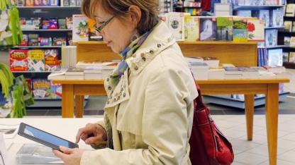 Eine Kundin betrachtet einen E-Book-Reader in einem Buchladen: Männer bevorzugen  Zeitungen, Frauen Romane.