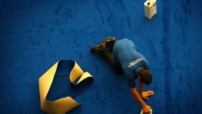 Ein Mann rollt in London einen Teppich aus.