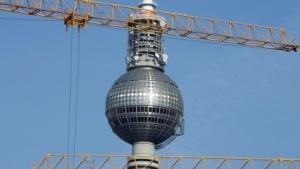 Der Berliner Fernsehturm mit Kränen im Vordergrund