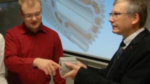 Ralf Werner (r) mit Elektromotor: Fertigung von Präzisionsbauteilen in hoher Stückzahl