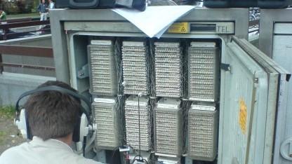 Techniker an einem Kabelverzweiger der Deutschen Telekom