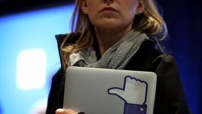 Eine Facebook-Mitarbeiterin mit einem Logo des Unternehmens auf ihrem Notebook