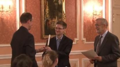 Edward Snowden (mi.) erhält von Thomas Drake (li.) und Ray McGovern das Symbol des Preises, eine Kerze, überreicht.