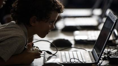 Ein Kind schaut auf ein Notebookdisplay.