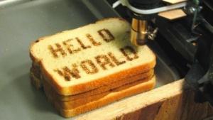 Ein CNC-gesteuerter Thermodrucker schreibt Hello World auf einen Toast.