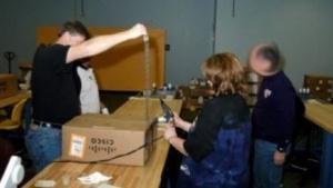 NSA-Mitarbeiter packen vorsichtig ein Cisco-Gerät aus.