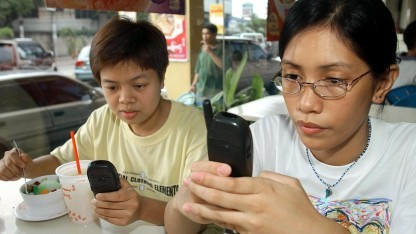 Teenager beim SMS-Schreiben in einem Restaurant in Manila
