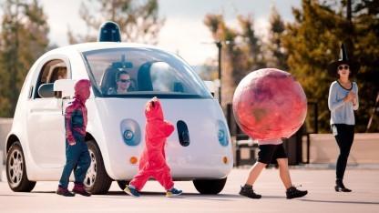 Google Auto vor Kindern in Halloween-Kostümierung.
