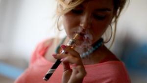 Frau mit E-Zigarette. Wer seinen Verdampfer mit anderen teilt, kann auch Viren übertragen.