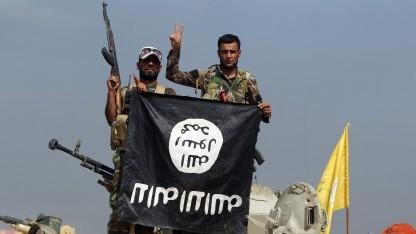 Irakische Soldaten präsentieren im Kampf gegen den Terrorismus eine Flagge des sogenannten islamischen Staates.