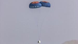 Die Passagierkapsel der New Shepard schwebt an zwei Fallschirmen zu Boden.