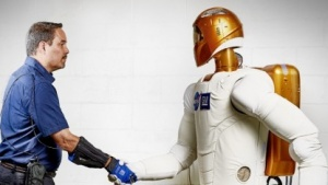 General-Motors-Manager schüttelt dem Robonaut 2 (R2) die Hand.