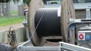 Das Glasfaserkabel wird sirrend von der Trommel gezogen.