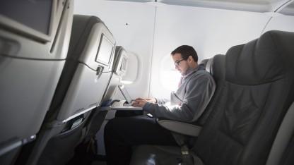 Ein Mann arbeitet im Flugzeug am Computer