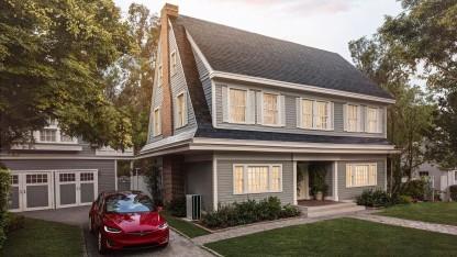 Ein mit einem Solar Roof ausgestattetes Dach mit passendem Tesla-Fahrzeug vorm Haus