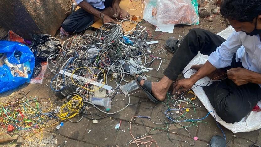 Schrotthändler holen im März 2021 Kupfer aus weggeworfenen Elektro- und Computerkabeln, um es an einem Straßenstand in Mumbai zu verkaufen.