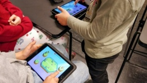 Zwei Schüler spielen Big Bang Legends, ein naturwissenschaftliches Lernspiel.
