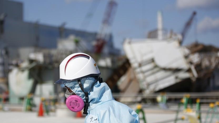 Ein Mitarbeiter mit Schutzkleidung vor dem zerstörten Block 1 des Atomkraftwerks Fukushima