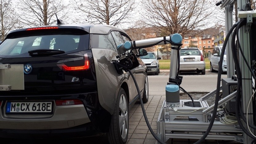 Roboter lädt autonom fahrende Elektroautos auf.