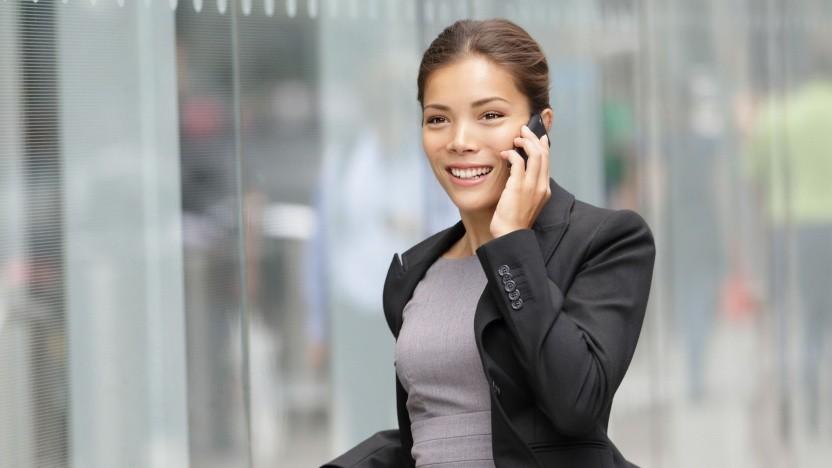 Frau telefoniert vor Glasfassade