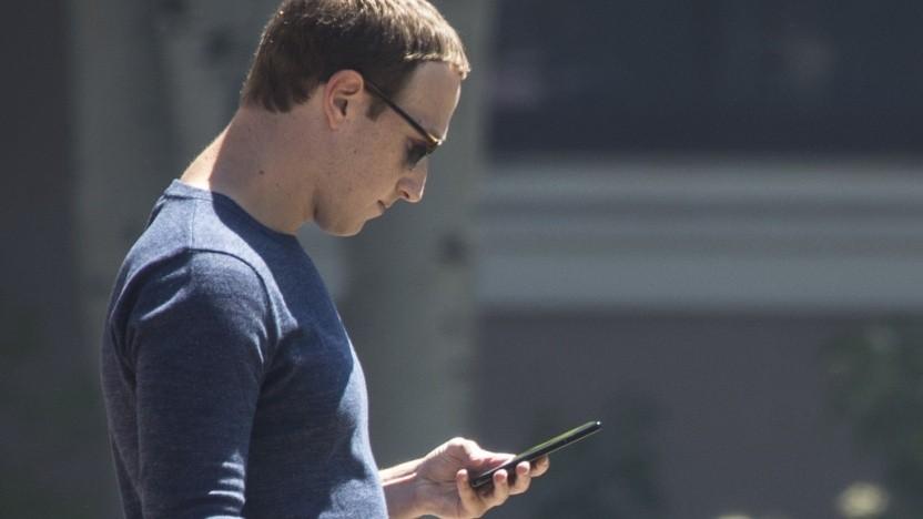 Facebook-Chef Mark Zuckerberg schaut auf sein Smartphone.