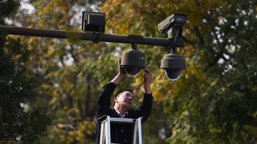 Ein Arbeiter stellt Überwachungskameras in Peking ein.