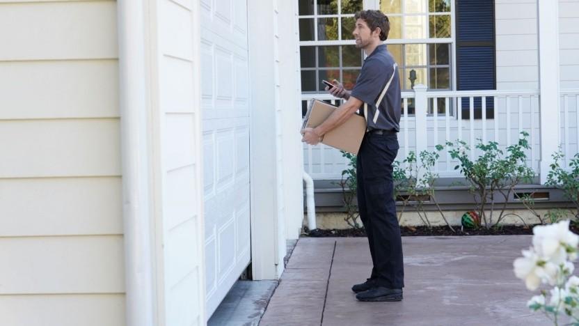 Ein Bote öffnet das Garagentor und legt das Amazon-Paket in der Garage ab.