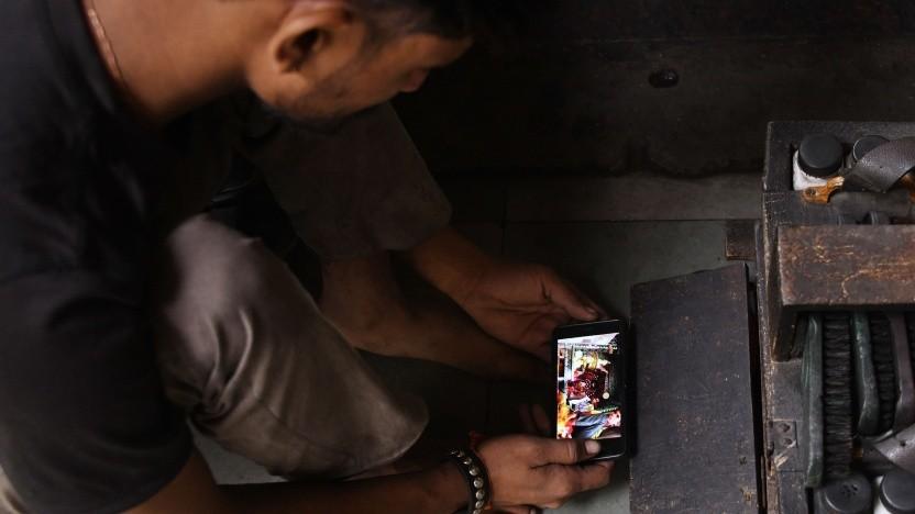 Ein indischer Schuhmacher mit seinem Smartphone