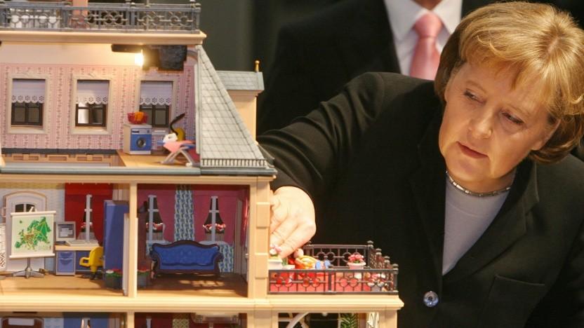 Kanzlerin Angela Merkel sieht sich ein Smart-Home-Spielmodell an.