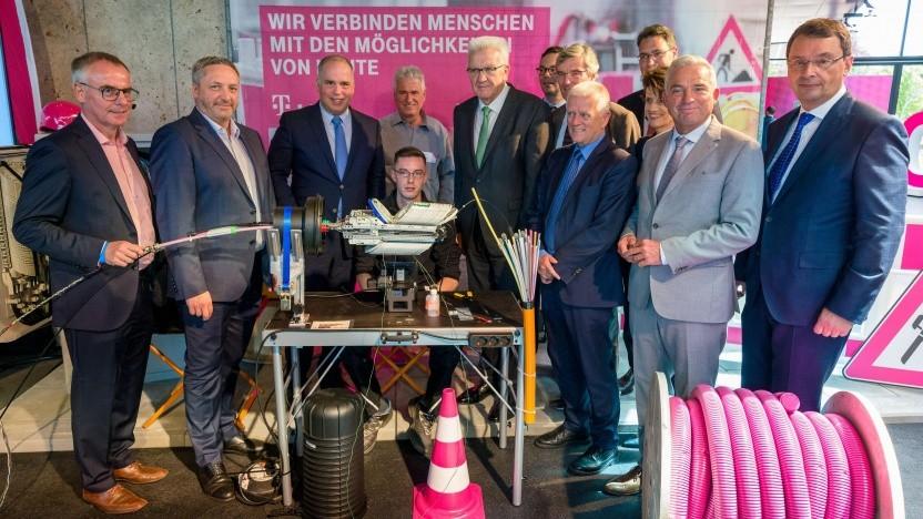 Glasfasermonteur Sven Bühler zeigt Ministerpräsident Winfried Kretschmann, Vertretern der Landkreise und Dirk Wössner (Telekom) das Spleißen.