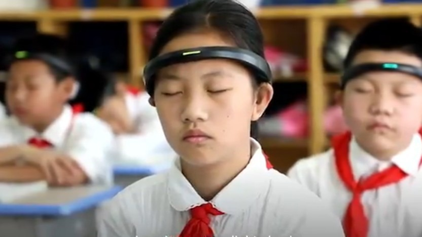Chinesische Kinder meditieren mit ihrem Gehirnwellensensor auf dem Kopf.