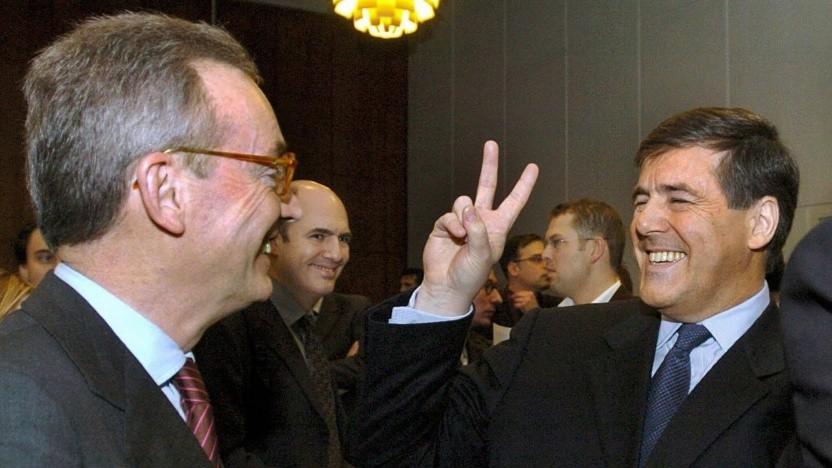 Ein Bild vom 21. Januar 2004 zeigt, wie der Vorsitzende der Deutschen Bank, Josef Ackermann (rechts), zu Beginn des Mannesmann-Prozesses in Düsseldorf ein V-Zeichen an den ehemaligen Mannesmann-Vorsitzenden, Klaus Esser (links), richtet.