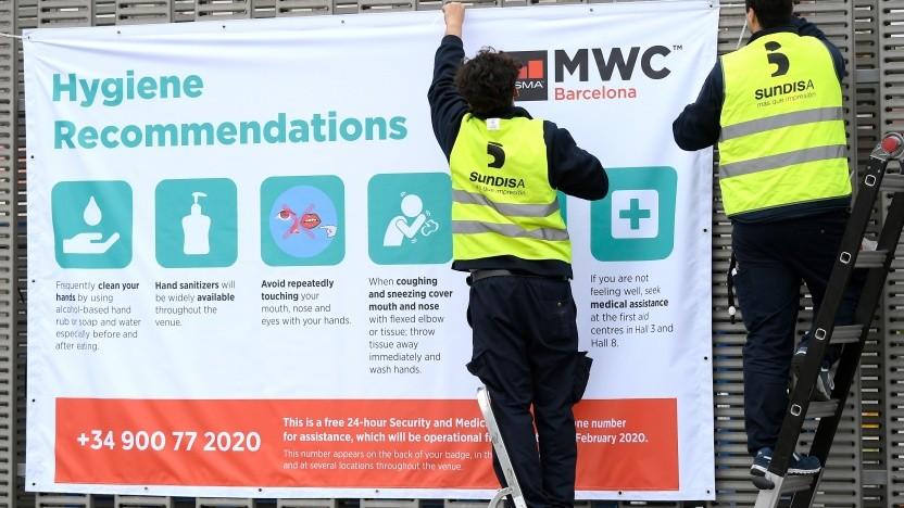 Arbeiter hängen ein Plakat mit Hygienehinweisen am MWC-Gelände in Barcelona auf.