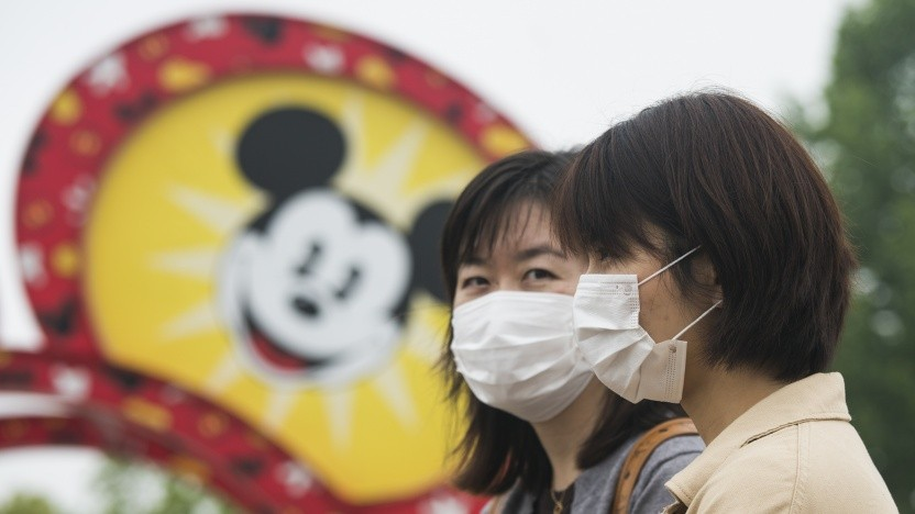 Touristen mit Schutzmasken im Disneyland Shanghai