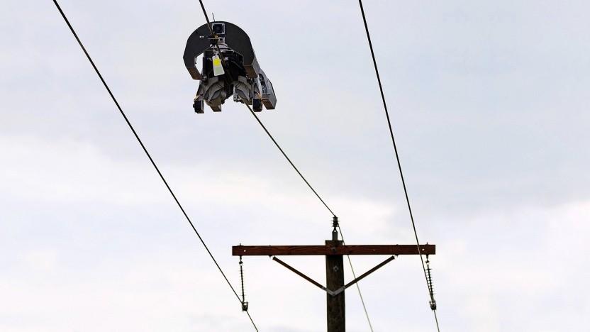 Ein Roboter verlegt Glasfaser auf einer Stromleitung.