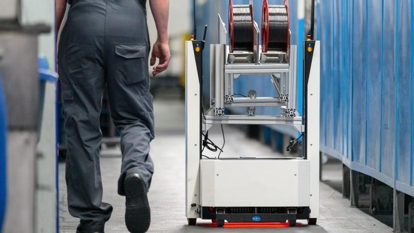 Arbeiter bei Osram und ein Fahrerloses Transportsystem (AGV) auf autonomer Fahrt
