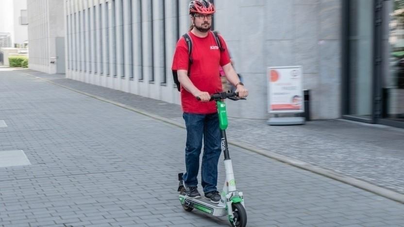 Ein Mann nutzt einen Lime-Scooter in Berlin