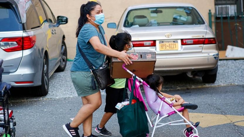 Mutter und ihre fünf- und dreijährigen Töchter verlassen im August 2020 eine Lebensmittelverteilung in Queens in New York.