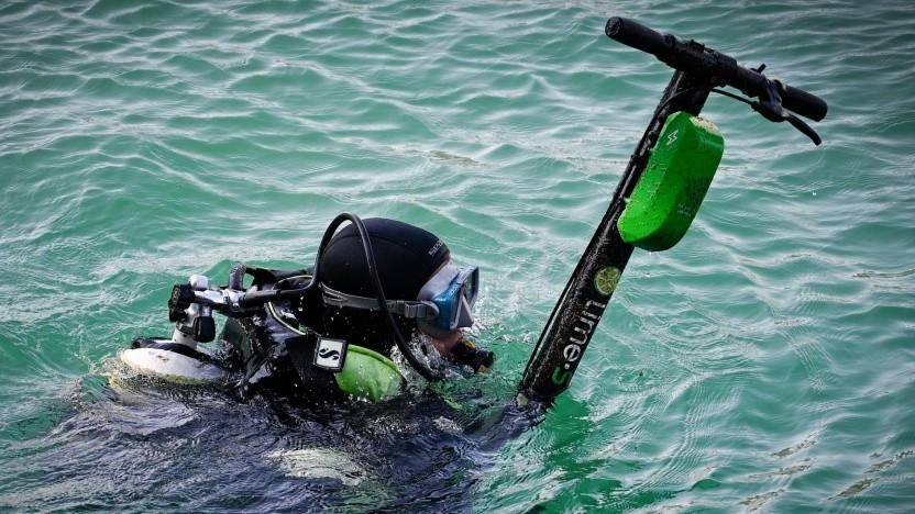 Ein Taucher fischt einen E-Scooter aus dem Meer.