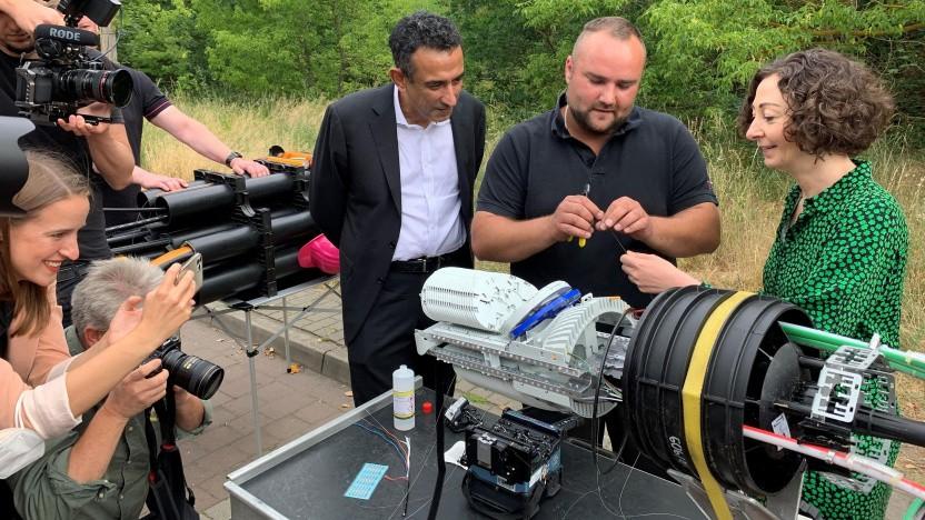 Wirtschaftssenatorin Ramona Pop (rechts) und Telekom-Deutschland-Vorstand Srini Gopalan lassen sich in Berlin-Karlshorst das Spleißen eines Glasfaserkabels erklären.